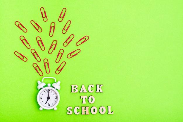 Обратно в школу. белые кольца будильника и текст деревянными буквами на зеленом фоне Premium Фотографии