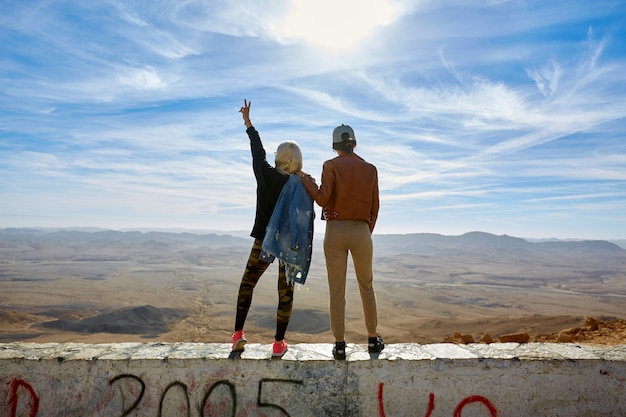 The back of two women, stand with their hands up overlooking the mountains. Premium Photo