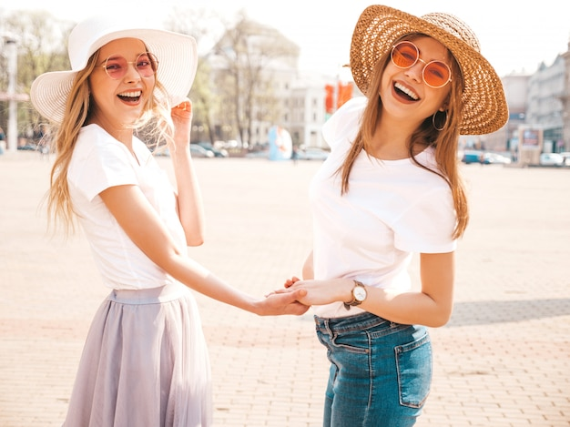 Back of two young beautiful blond smiling hipster girls in trendy summer white t-shirt clothes and hat.  . couple holding each other hands Free Photo