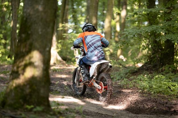 フォレストでバイクに乗ってアクティブな男の背面図 無料写真