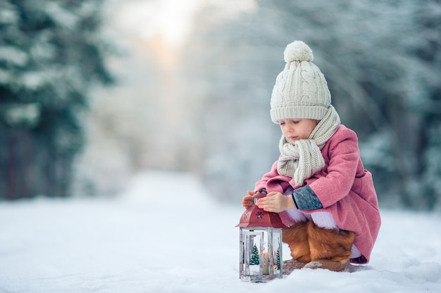 Back view of adorable girl with flashlight on christmas outdoors Premium Photo
