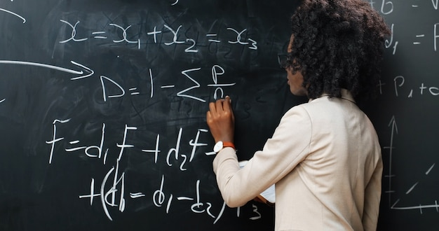 Back view on african american young woman teacher at school writing formulas and mathematics laws on blackboard. school concept. female lecturer in glasses explaining physics laws. rear. Premium Photo