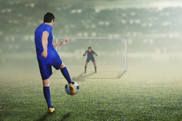 Back view of asian football player man in action Premium Photo