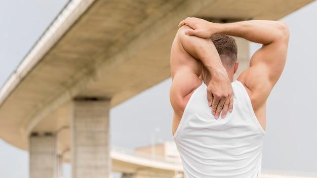 Back view athletic man stretching Premium Photo