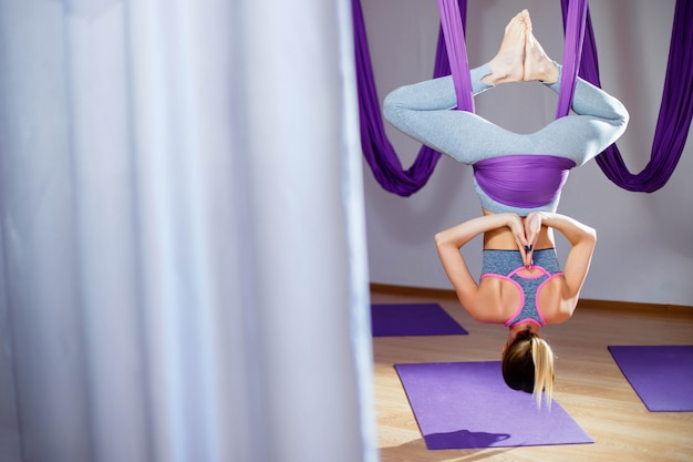 Back view of attractive young woman doing pose of antigravity yoga Premium Photo