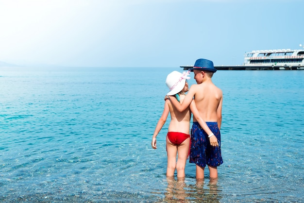 Back view of babygirl and babyboy kissing on the beach in straw hats at the seaside. Premium Photo