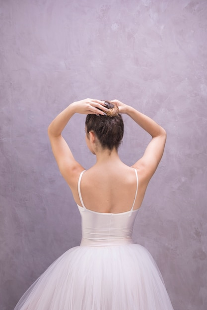 Back view ballerina fixing bun hairstyle Free Photo