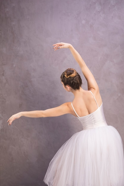 Back view ballerina posing with stucco background Free Photo