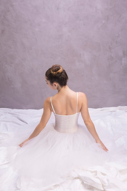Back view ballerina sitting Free Photo