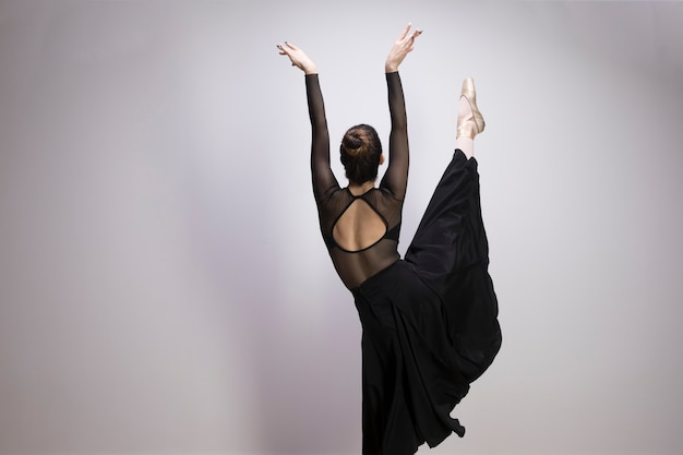 Back view ballerina with one leg up Free Photo