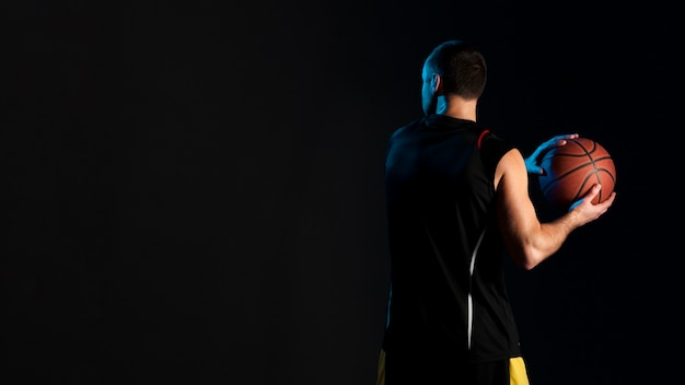 Back view of basketball player with ball and copy space Free Photo