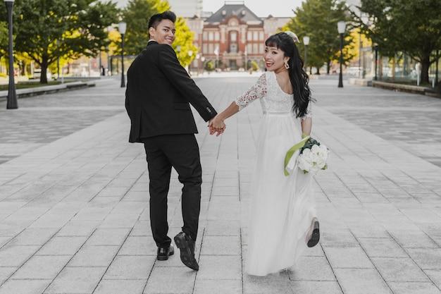 Vista posteriore della sposa e dello sposo che camminano per strada tenendo le mani Foto Gratuite