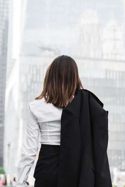 Vista posteriore donna d'affari in possesso di un rivestimento Foto Gratuite