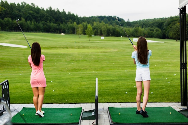 Back view of casual girls at a golf field Free Photo