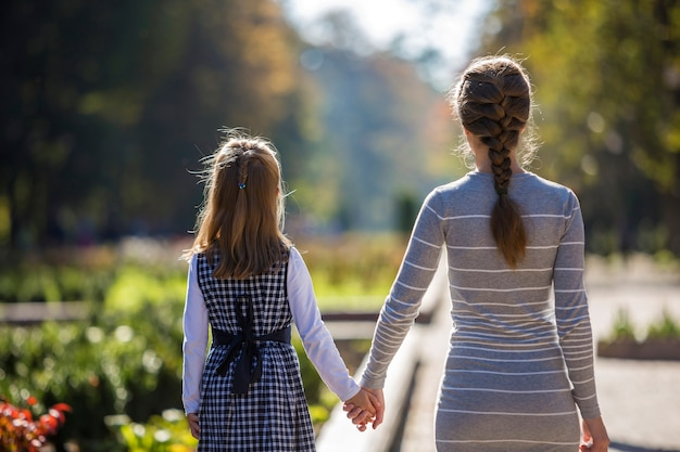 Back view of child girl and mother in dresses together holding hands on warm day outdoors on sunny. Premium Photo