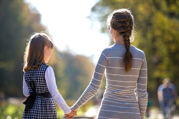 Back view of child girl and mother holding hands Premium Photo