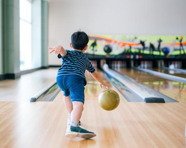Back view child throwing bowling ball   Premium Photo