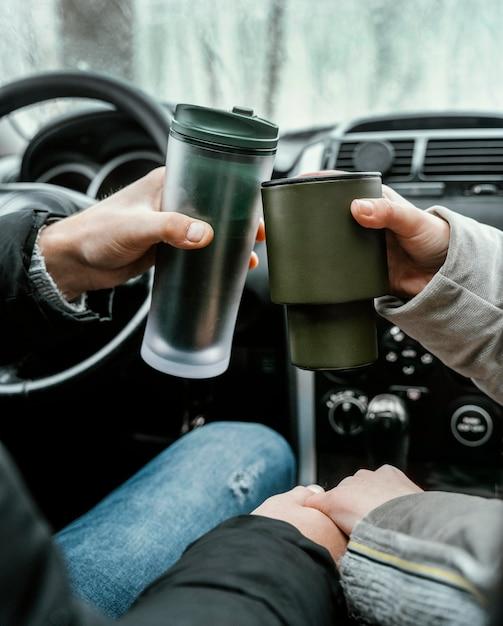 Vista posteriore della coppia in macchina durante un viaggio brindando con bevande calde Foto Gratuite