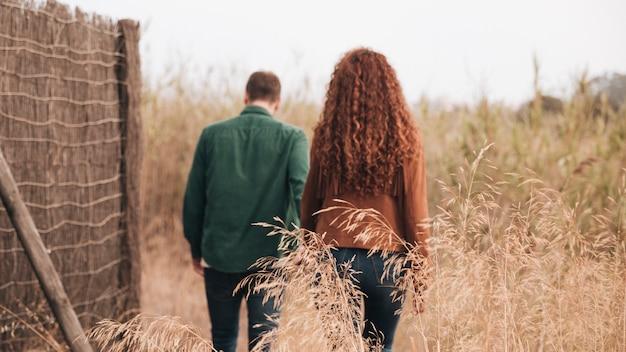 Back view couple walking through wheat field Free Photo
