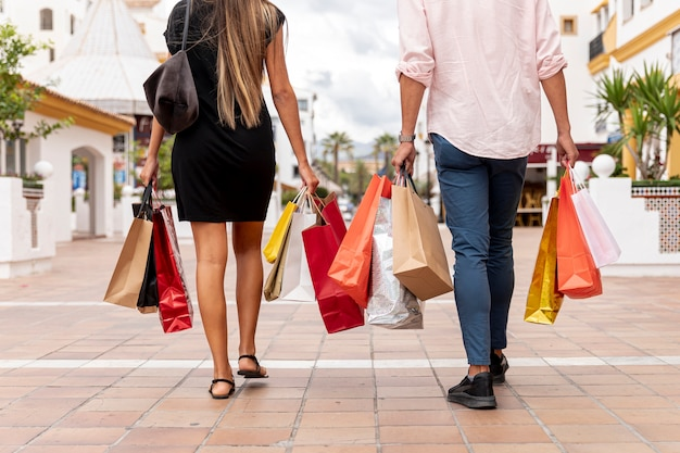 Back view of couple with shopping bags Free Photo