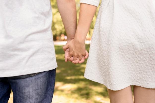 Vista posteriore della coppia carina mano nella mano mentre nel parco Foto Gratuite