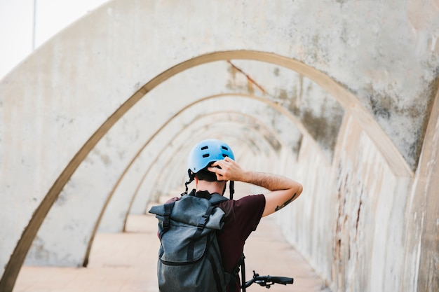 Back view of a cyclist putting on his helmet Free Photo