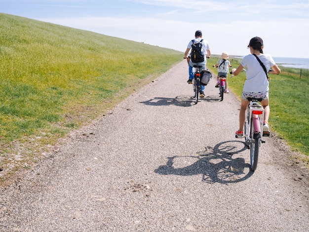 Back view cyclists family traveling on the road in the dune area of schiermonnikoog island. Premium Photo
