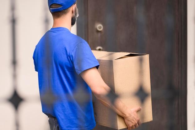 Vista posteriore consegna uomo che trasportano la spedizione Foto Gratuite