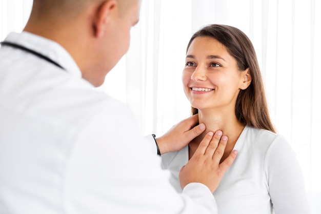 Back view doctor examining woman neck Free Photo