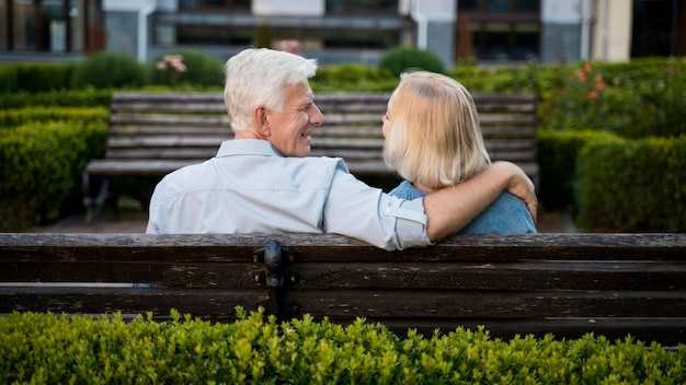Back view of embraced older couple outdoors on bench Free Photo