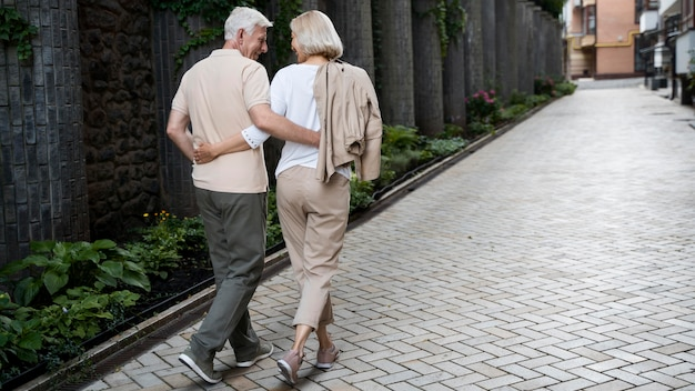 Back view of embraced senior couple taking a walk outdoors Premium Photo