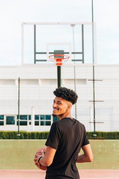 Back view of ethnic cheerful young man on basketball court Free Photo