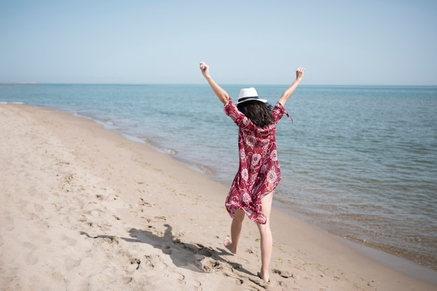 Back view excited woman walking at seashore Free Photo
