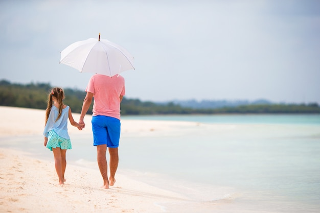 Back view of family at beach with umbrella Premium Photo