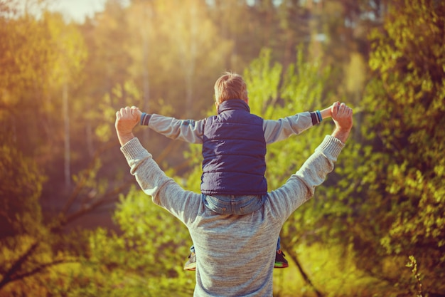 Back view of father  his son on shoulders on nature. Premium Photo
