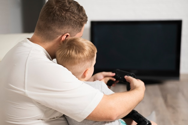 Back view father and son playing video games Free Photo