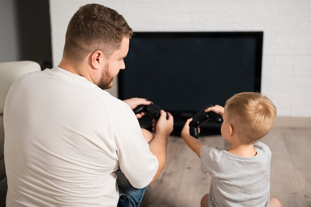 Back view father and son playing with controllers close-up Free Photo