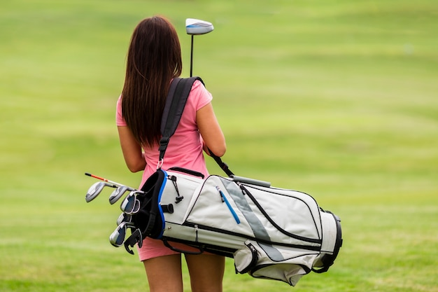 Back view fit young woman with golf clubs Free Photo
