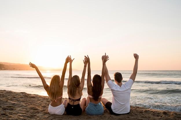 Amici di vista posteriore che tengono le mani in alto Foto Gratuite