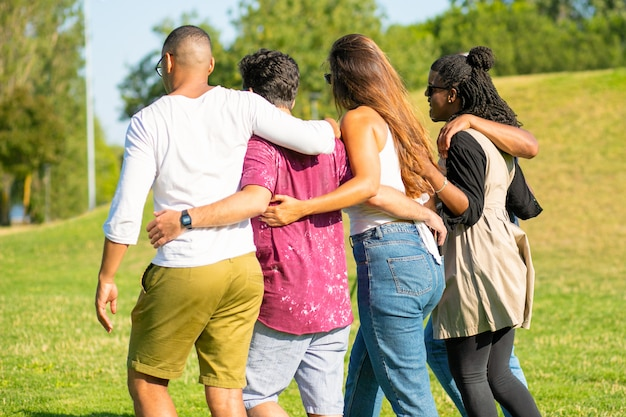 Back view of friends hugging while strolling on meadow. young people talking while walking together. friendship concept Free Photo
