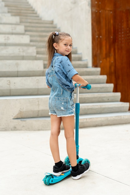 Back view of girl riding blue scooter Free Photo