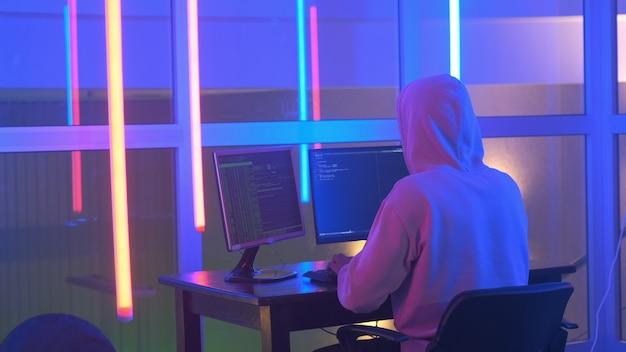 Tampak belakang peretas dalam sistem jaringan tembus hoodie putih di ruang neon Foto Premium