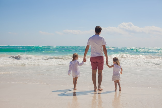 Back view of happy father and his adorable little daughters walking on sunny day Premium Photo