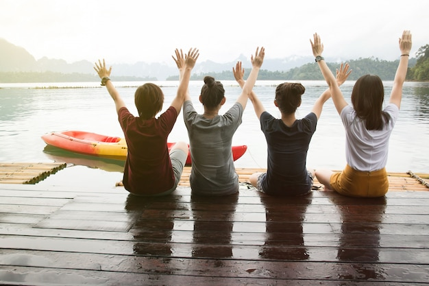 Back view of happy young friends sits on the raft and having enjoy the sunny day. travel concept. Premium Photo