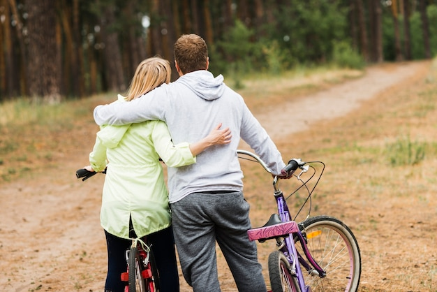 Back view hugging couple with bicycles Free Photo