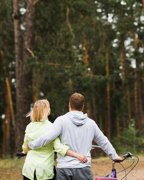 Back view hugging couple with forest background Free Photo