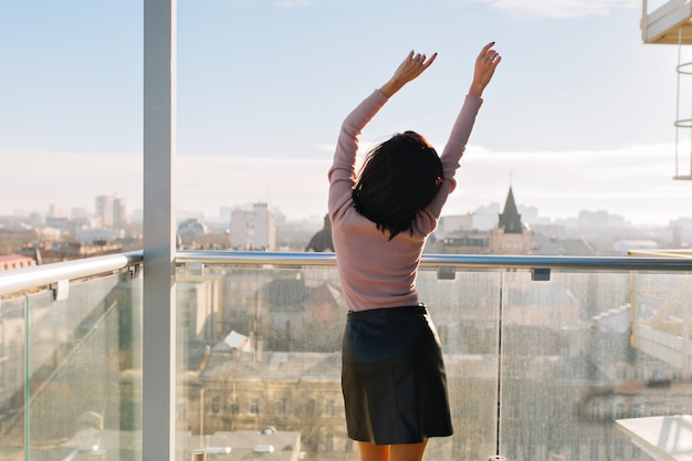 Back view joyful young attractive woman stretching on terrace in sunny morning on big city view. woman, great success, happiness, relax, cheerful mood, Free Photo