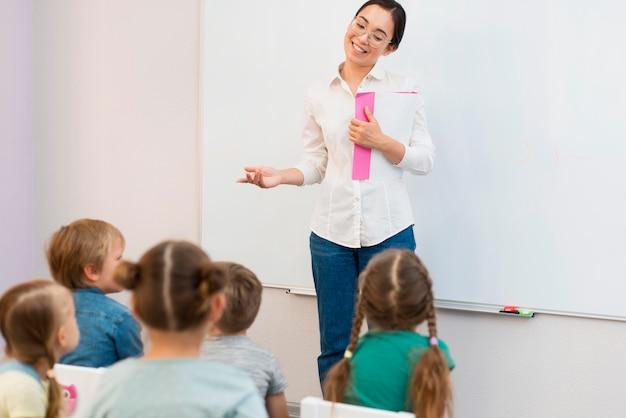 Дети вид сзади обращают внимание на своего учителя во время урока Premium Фотографии