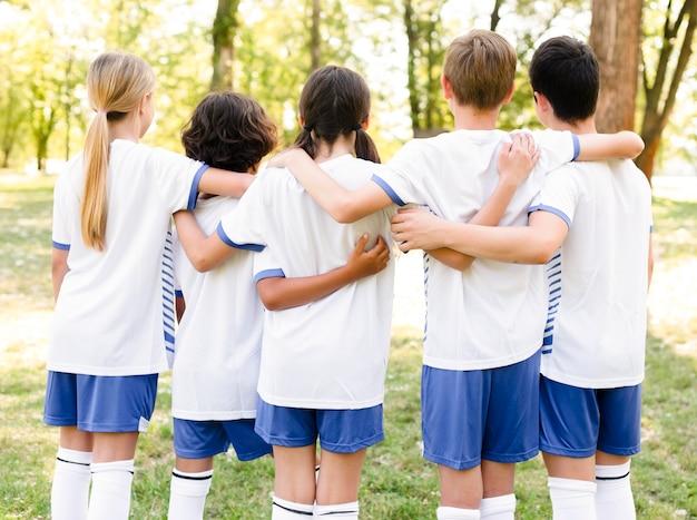 Vista posteriore di bambini in abiti sportivi che si tengono l'un l'altro Foto Gratuite