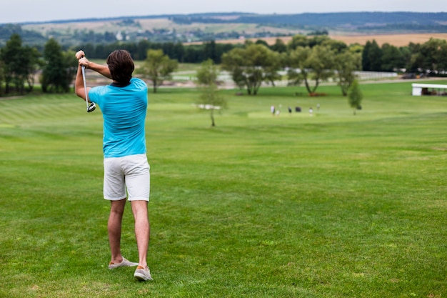Back view male golf player on professional golf course Free Photo